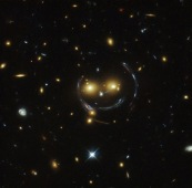 """In the centre of this image, taken with the NASA/ESA Hubble Space Telescope, is the galaxy cluster SDSS J1038+4849 — and it seems to be smiling. You can make out its two orange eyes and white button nose. In the case of this """"happy face"""", the two eyes are very bright galaxies and the misleading smile lines are actually arcs caused by an effect known as strong gravitational lensing. Galaxy clusters are the most massive structures in the Universe and exert such a powerful gravitational pull that they warp the spacetime around them and act as cosmic lenses which can magnify, distort and bend the light behind them. This phenomenon, crucial to many of Hubble's discoveries, can be explained by Einstein's theory of general relativity. In this special case of gravitational lensing, a ring — known as an Einstein Ring — is produced from this bending of light, a consequence of the exact and symmetrical alignment of the source, lens and observer and resulting in the ring-like structure we see here. Hubble has provided astronomers with the tools to probe these massive galaxies and model their lensing effects, allowing us to peer further into the early Universe than ever before. This object was studied by Hubble's Wide Field and Planetary Camera 2 (WFPC2) and WideField Camera 3 (WFC3) as part of a survey of strong lenses. A version of this image was entered into the Hubble's Hidden Treasures image processing competition by contestant Judy Schmidt."""